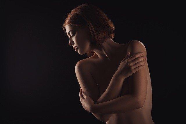 Nahá žena s krátkymi hnedými vlasmi si zakrýva prsia.jpg
